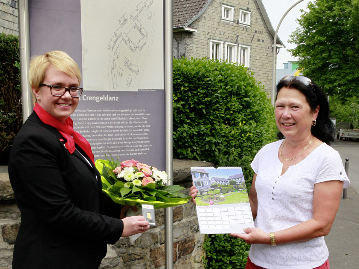 """Cornelia Rüsing (rechts) ist die Gewinnerin des April-Rätsels im Sparkassenkalender 2015. Vor dem Eingang zur """"Gartenstadt Crengeldanz"""" an der unteren Schottstraße gratulierte Stefanie Matuschek, Leiterin der benachbarten Sparkassengeschäftsstelle, mit einem Blumenstrauß und übergab einen 5-Gramm-Goldbarren."""